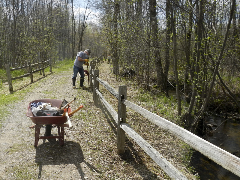 Doug Seidl fixing fence posts along trail