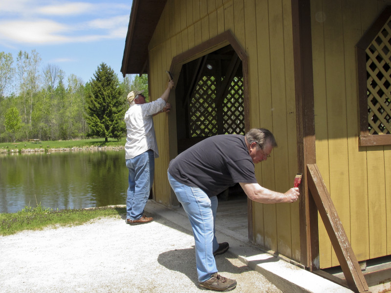 Jack Koivisto and Paul Mongin scraping paint off covered bridge