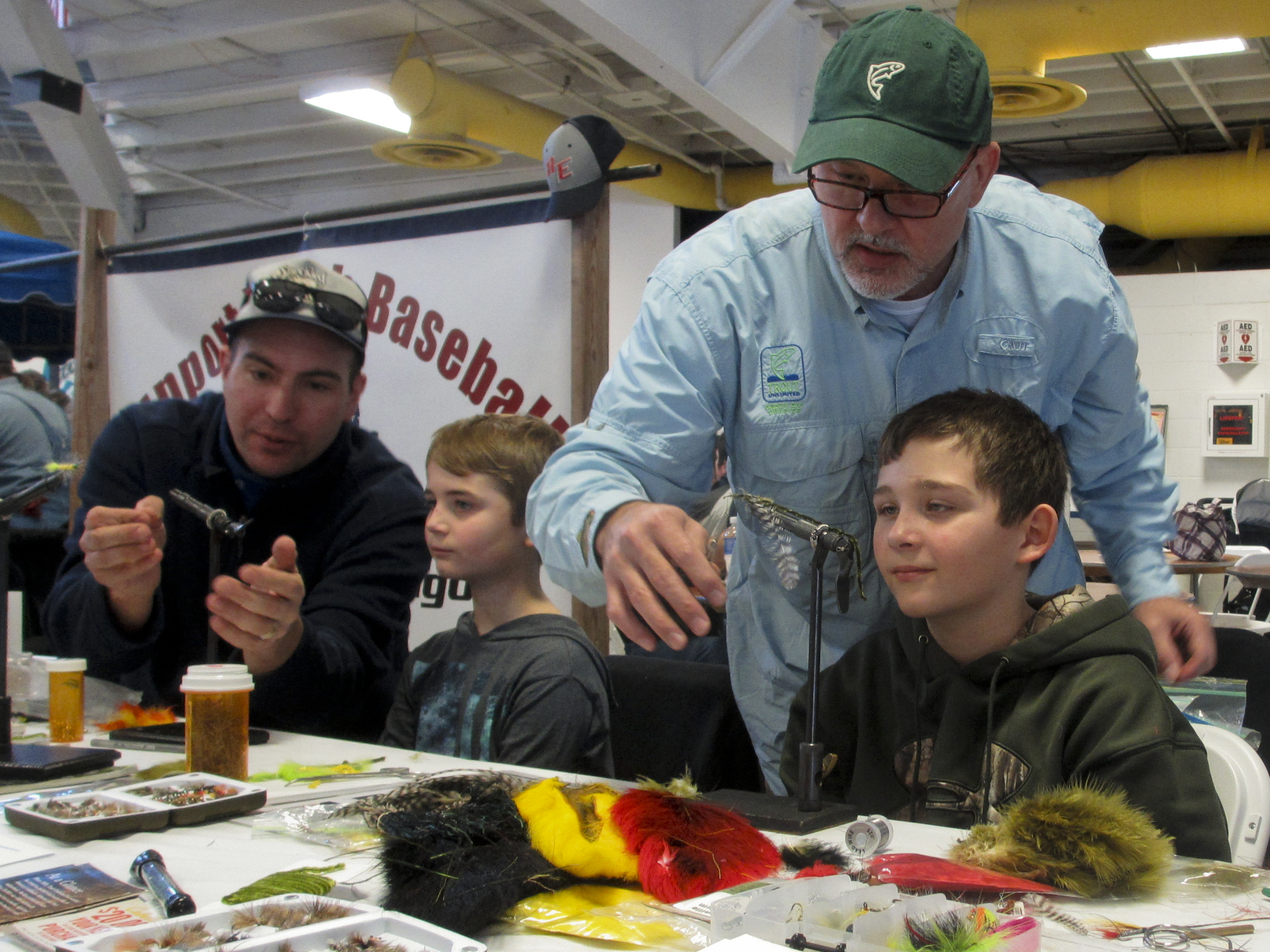Adrian Meseberg and Mike Renish tying flies with youth at Sunnyview Expo Center outside Oshkosh