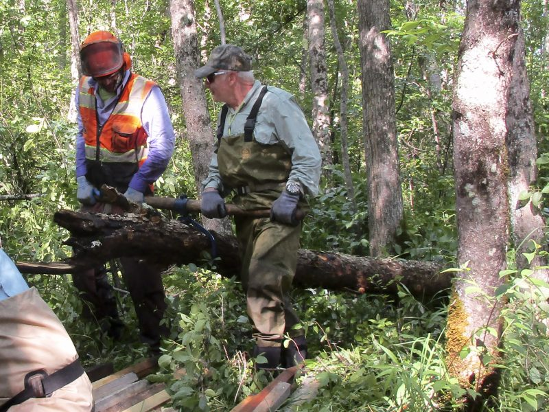 Kyle Siebers and Wayne Czypinski drag another log out of woods